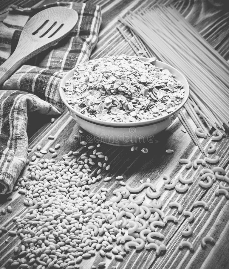 Der Garprozess Eine Schüssel des rohen Hafermehls, Getreide, Teigwaren, Holz stockbilder