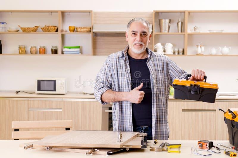 Der gealterte Auftragnehmerschlosser, der in der Küche arbeitet stockfotografie