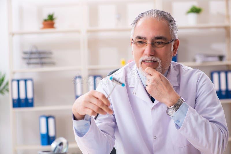 Der gealterte männliche Doktor mit Hammer lizenzfreie stockfotografie