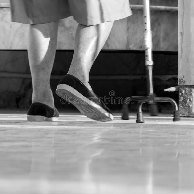 Der Gebrauch des alten Mannes ein Spazierstock lizenzfreie stockbilder