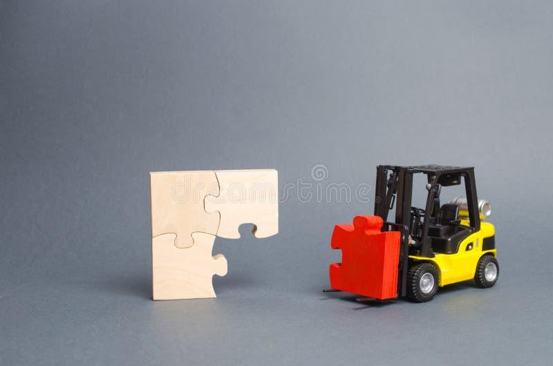 Der gelbe Gabelstapler holt das fehlende rote Puzzlespiel zum unfertigen Bau Fertigstellung des Projektes, ein Schlüsselelement stockbild