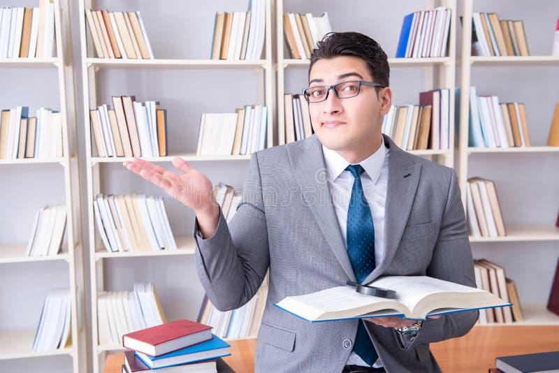 Der Geschäftsjurastudent mit Lupe ein Buch lesend lizenzfreie stockbilder