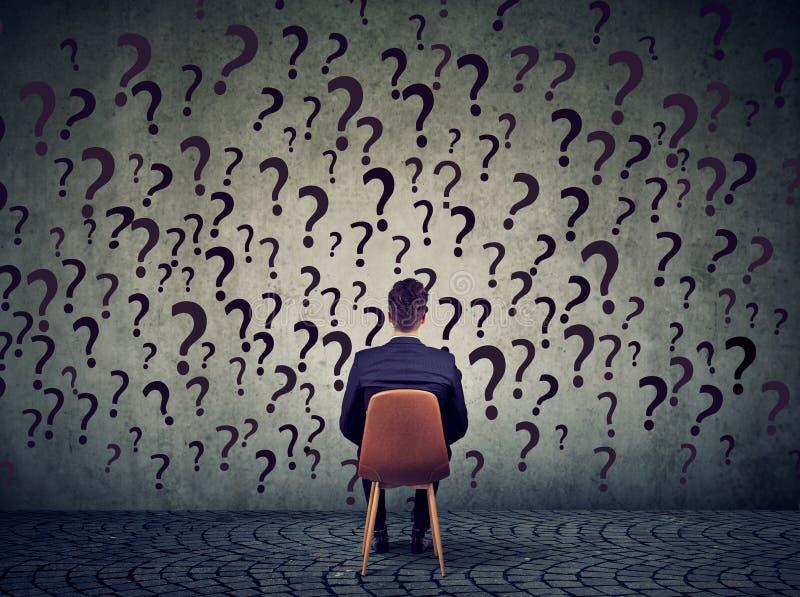 Der Geschäftsmann, der auf einem Stuhl vor einer Wand sitzt, hat viele Fragen und wundert sich was, als Nächstes zu tun lizenzfreie stockfotografie