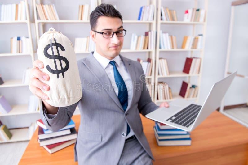 Der Geschäftsmann in der Bibliothek mit einem Geldsack und einem Laptop stockfotografie