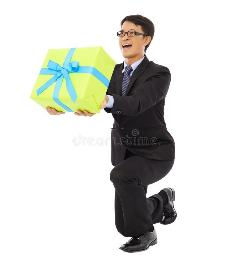 Der Geschäftsmann, der eine Geschenkbox hält und knien unten lizenzfreie stockfotos