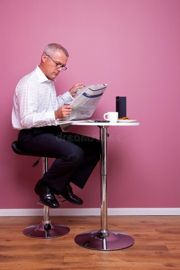 Der Geschäftsmann, der eine Zeitung liest, saß in einem Kaffee stockbilder