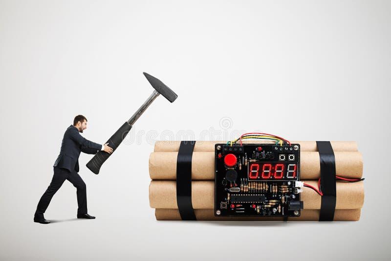 Der Geschäftsmann, der großen Hammer hält und bereiten zum Entschärfen der großen Bombe vor lizenzfreie stockbilder