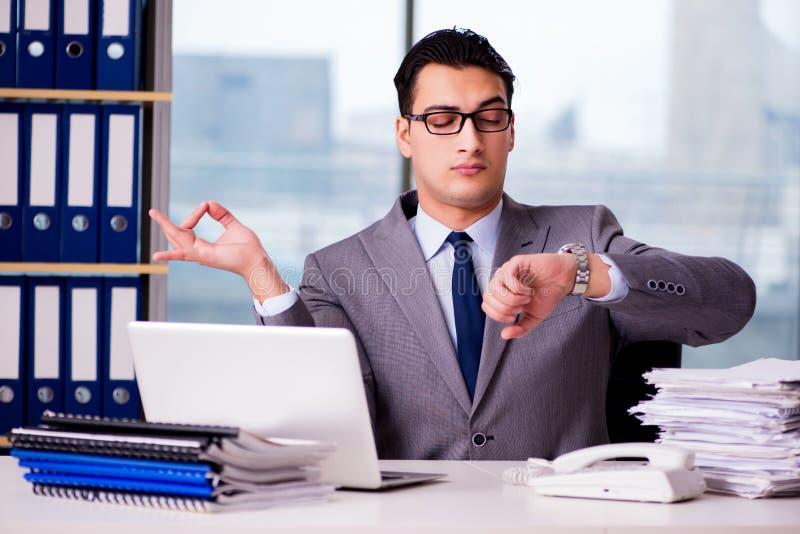 Der Geschäftsmann, der im Büro meditiert lizenzfreie stockfotos