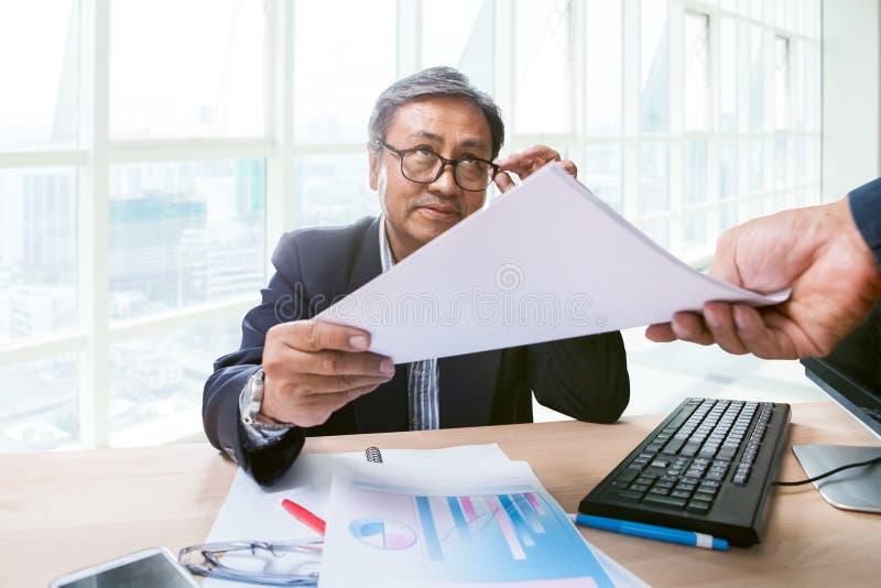 Der Geschäftsmann, der im Funktionstabellenbüro sitzen und das Papier berichten herein lizenzfreie stockfotos