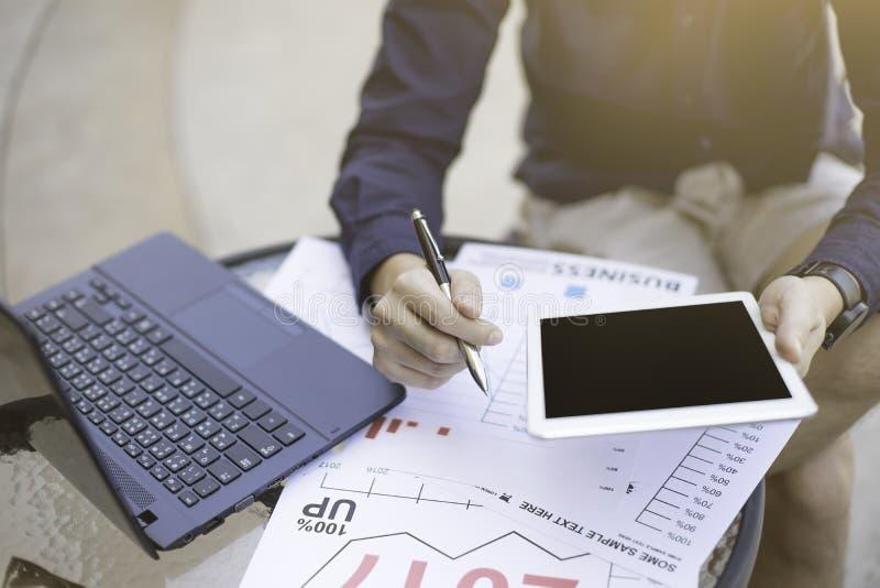 Der Geschäftsmann, der Laptop und Smartphone verwenden und die Tablette für analytisches Finanzdiagrammjahr 2017 neigen die Vorau stockfoto