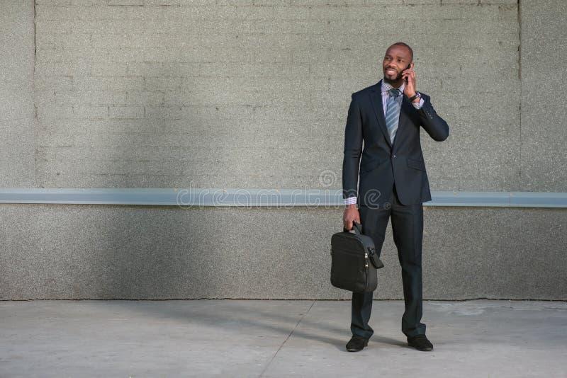Der Geschäftsmann, der mit seinem Aktenkoffer und ihm steht, benutzt das Telefon stockfoto