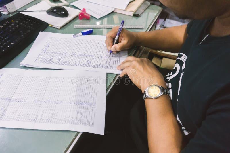 Der Geschäftsmann, der am Schreibtisch sitzt und benutzen einen Stift schreiben auf Papier stockfotografie