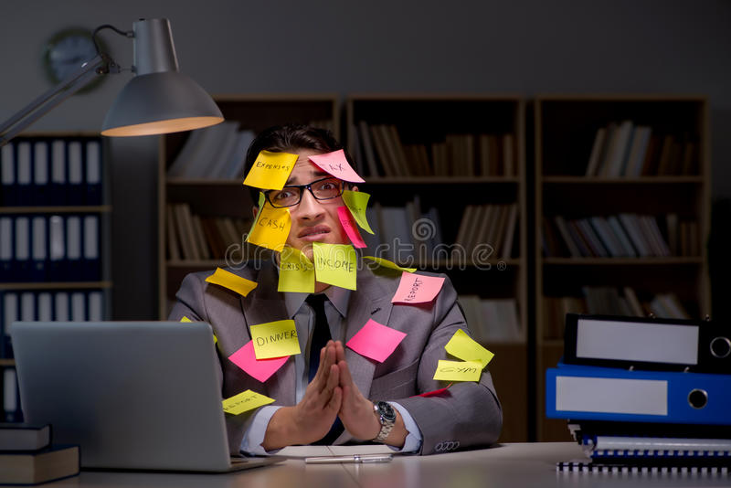 Der Geschäftsmann, der spät bleibt, um Prioritäten heraus zu sortieren lizenzfreie stockfotos