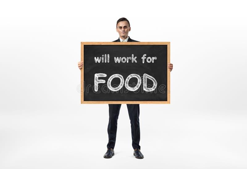 Der Geschäftsmann, der Tafel mit Wörter ` steht und hält, arbeitet für Lebensmittel `, das auf es geschrieben wird lizenzfreie stockbilder