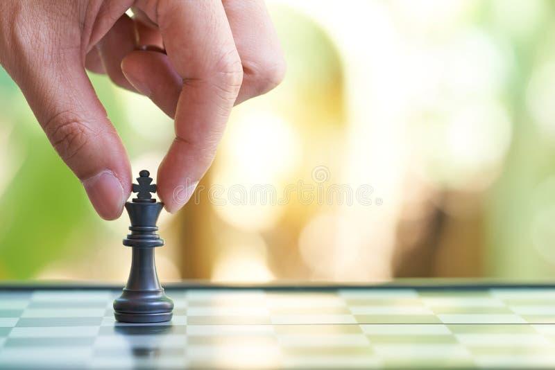 Der Geschäftsmann, der einen König Chess hält, wird auf ein Schachbrett gesetzt Anwendung als Hintergrundgeschäftskonzept und Str lizenzfreie stockfotos