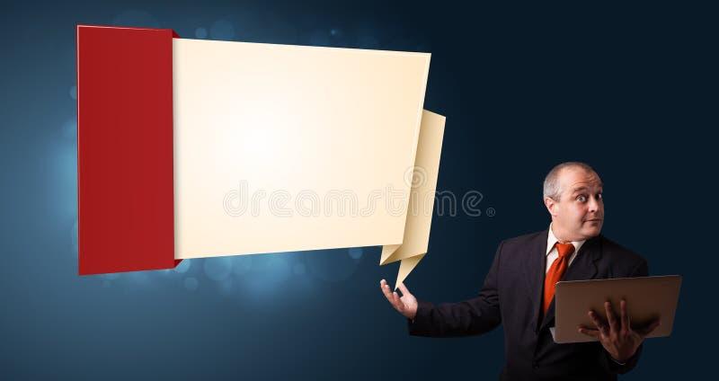 Der Geschäftsmann, der einen Laptop hält und modernen Origami darstellt, kopieren stockbilder