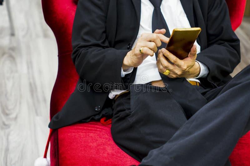 Der Geschäftsmann, der einen schwarzen Anzug sitzt auf einem roten Samtstuhl, Touch Screen Smartphone, während des Bruches trägt, lizenzfreie stockfotografie