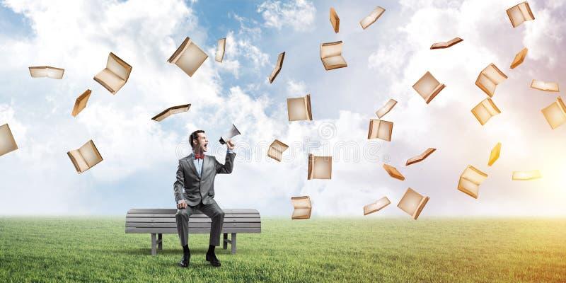 Der Geschäftsmann im Sommerpark etwas im Lautsprecher ankündigend und die Bücher fliegen herum lizenzfreies stockfoto