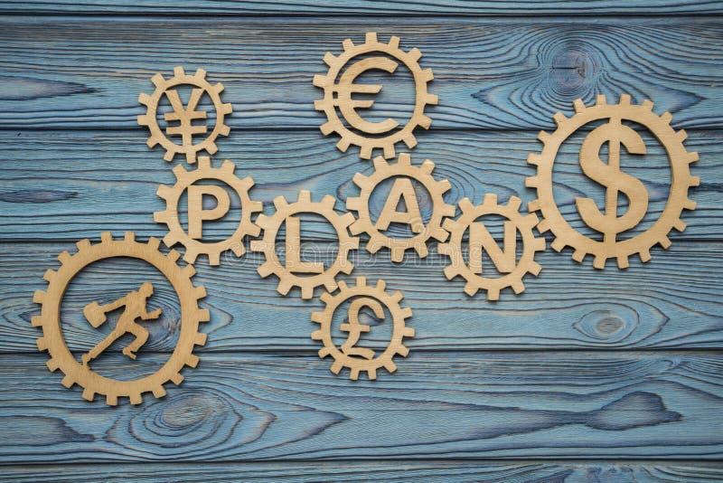 Der Geschäftsmann lässt ein Puzzlespiel im Gang mit dem Wort PLAN und Symbole von Gelddollar, Euro, Yen, Pfundsterling laufen lizenzfreies stockfoto
