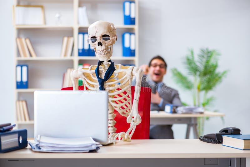 Der Geschäftsmann, der mit dem Skelett im Büro arbeitet lizenzfreie stockfotos