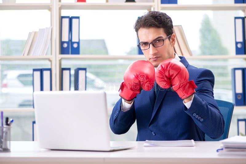 Der Geschäftsmann mit den Boxhandschuhen verärgert im Büro lizenzfreies stockfoto