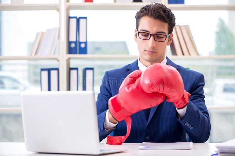 Der Geschäftsmann mit den Boxhandschuhen verärgert im Büro stockbilder