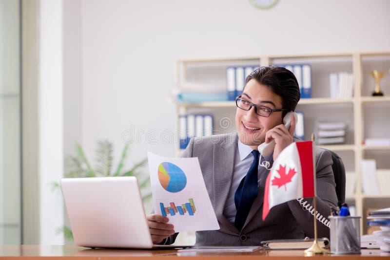 Der Geschäftsmann mit kanadischer Flagge im Büro lizenzfreie stockfotografie