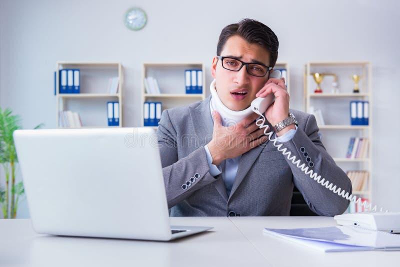 Der Geschäftsmann mit der Nackenverletzung, die im Büro arbeitet lizenzfreies stockbild