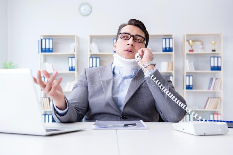 Der Geschäftsmann mit der Nackenverletzung, die im Büro arbeitet lizenzfreie stockfotografie