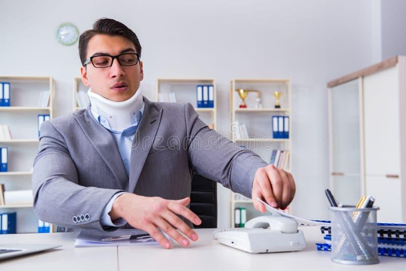 Der Geschäftsmann mit der Nackenverletzung, die im Büro arbeitet stockbild
