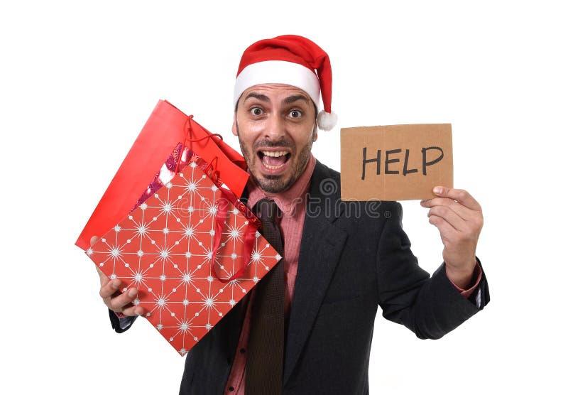 Der Geschäftsmann in Santa Claus-Hut, der Einkaufstaschen bitten um Hilfe beim Pappzeichen hält, sorgte sich stockfotos
