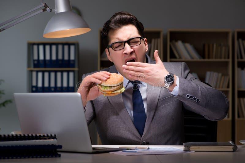 Der Geschäftsmann spät nachts einen Burger essend stockbild
