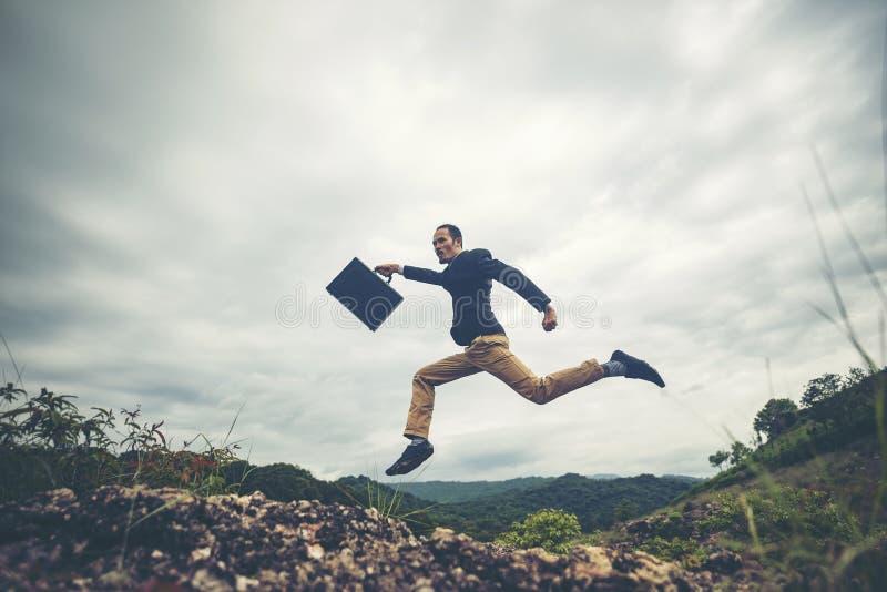 Der Geschäftsmann springend über den Berg, Geschäftsarbeitskraftkonzept lizenzfreie stockfotos