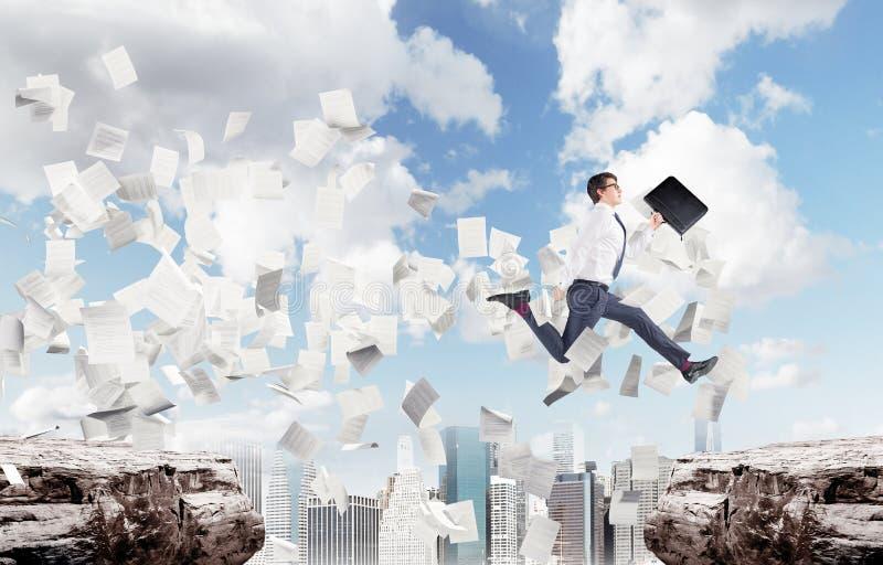 Der Geschäftsmann springend über einen Abgrund in einer Stadt, Papiere stockbilder