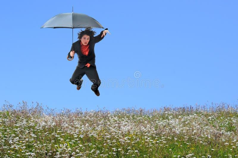 Der Geschäftsmann springend über Gras-Hügel stockfotografie
