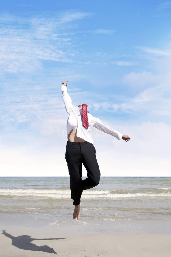 Der Geschäftsmann springend am Strand