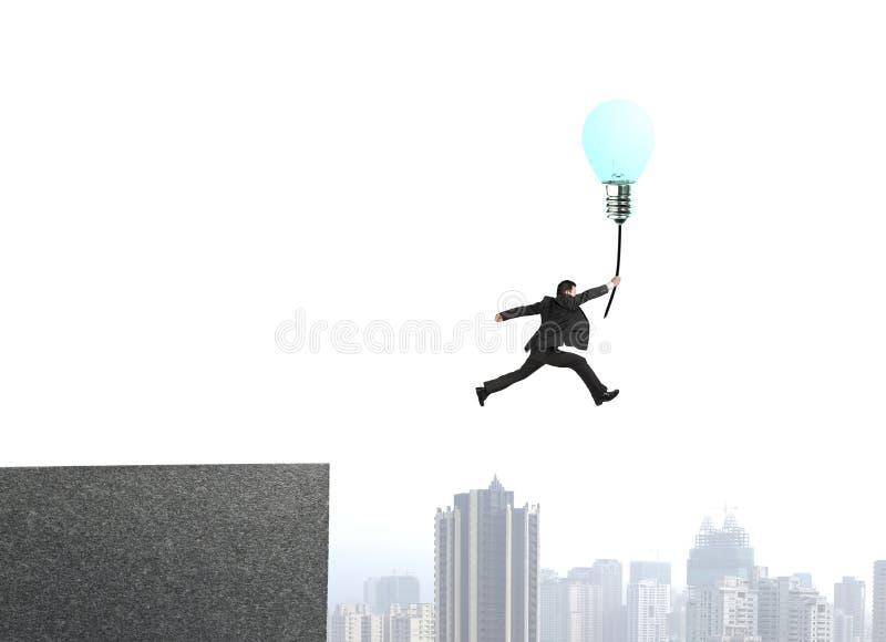 Der Geschäftsmann springend von bulding Spitze, um glühende Lampe ballo zu fangen stockfoto