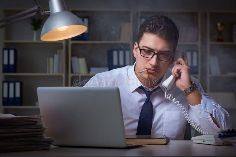 Der Geschäftsmann, der am Telefon spricht und im Büro raucht lizenzfreies stockfoto