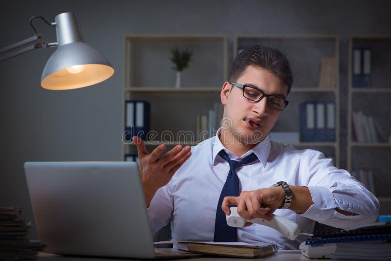 Der Geschäftsmann, der am Telefon spricht und im Büro raucht stockfoto