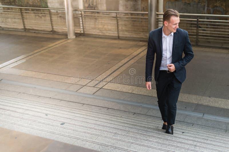 Der Geschäftsmann tragen schwarzen Anzug gehend, Treppe in modernem steigernd lizenzfreie stockfotografie