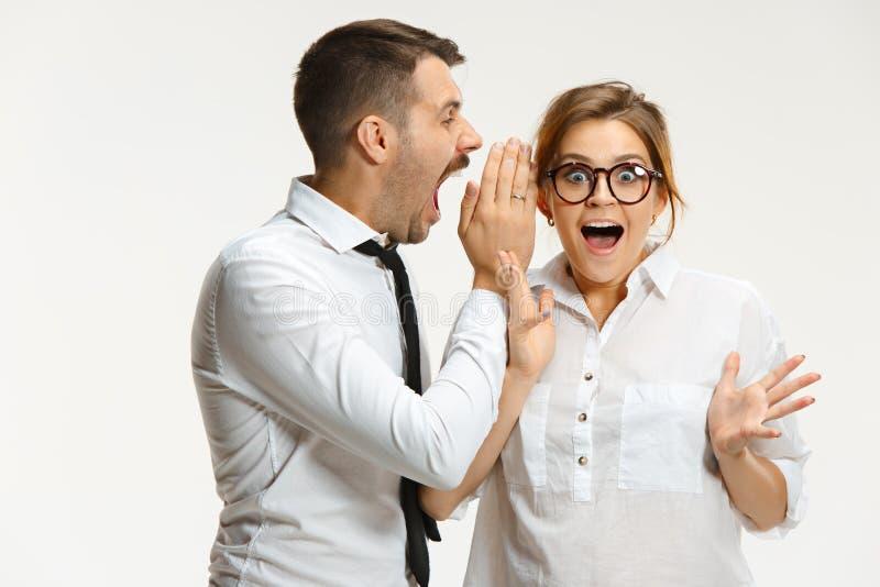 Der Geschäftsmann und die Frau, die auf einem grauen Hintergrund in Verbindung stehen stockbilder