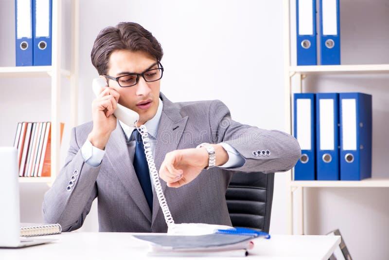 Der Geschäftsmannangestellte, der am Bürotelefon spricht stockbilder