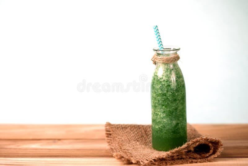 Der gesunde frische grüne Smoothiesaft in der Glasflasche auf Holz lizenzfreie stockfotografie