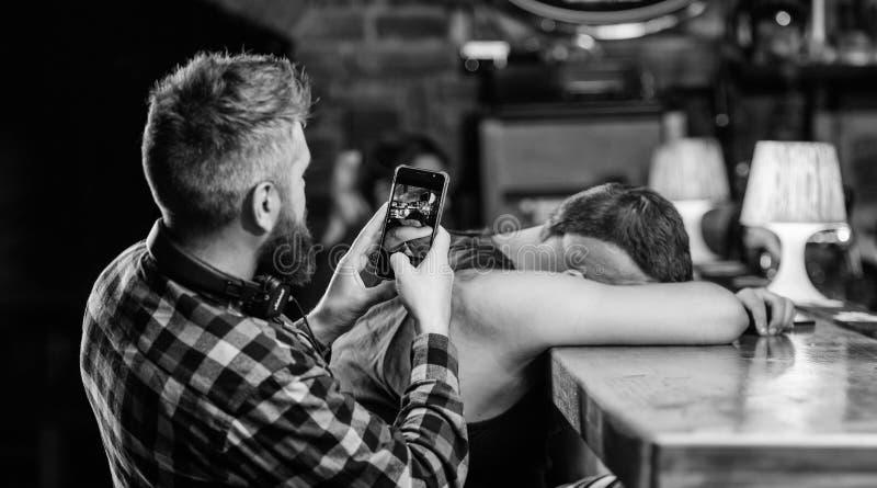 Der getrunkene Mann schlafen und Kerl mit Smartphone ein Hippie, der Foto betrunkenen Freund nimmt Betrunkene Freunde in der Bar  lizenzfreies stockfoto