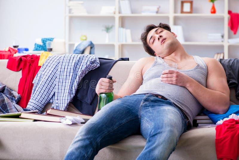 Der getrunkene trinkende Alkohol des jungen Mannes Student in einem unordentlichen Raum stockbild