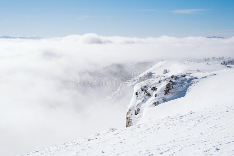 Der Gipfel eines schneebedeckten Berges mit einem klaren blauen Himmel an einem sonnigen Tag das Tal übersehend bedeckt durch Neb stockfotografie