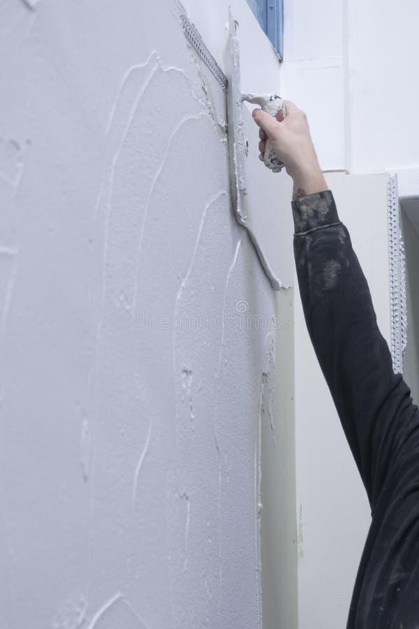 Der Gipser klebt mit seinem rechten Arm auf die Wand mit dem Pflaster stockbilder