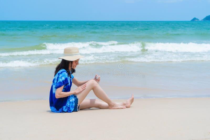 Der glückliche Asiatinabnutzungslichtschutz, zum ihrer Haut am Strand während der Reisefeiertage zu schützen macht draußen in Oze stockfotografie