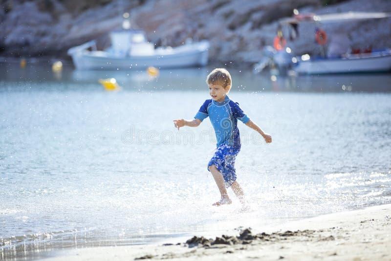 Der glückliche entlang Wasserrand laufende und machende Junge spritzt stockfotos