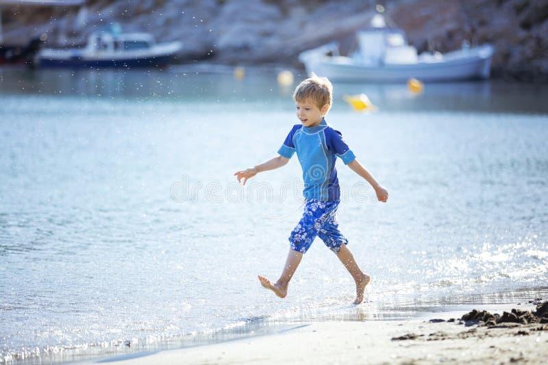 Der glückliche entlang Wasserrand laufende und machende Junge spritzt lizenzfreie stockfotografie
